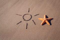 Big orange starfish and sun drawing on sheashore Royalty Free Stock Photography