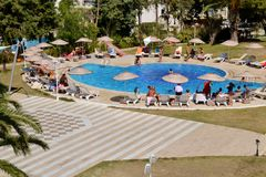 Big Outdoor Luxury Pool Area in a Big Hotel. Bodum ,TURKEY-15.07.17-Big Outdoor blue pool with palms,sunbeds and umbrellas stock images