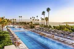 Big Outdoor pool with  palms and sea in background .Sunset sky Royalty Free Stock Photo