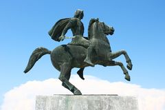 Warrior on a horse oxidized bronze statue. Big oxidized bronze statue of a Greek warrior on a horse, with a small sword in his hand and a waving cloak on the stock photos