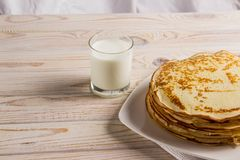 A big pack of delicious pancakes on a white plate with milk stock photos