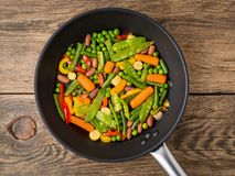 Big pan fried with colorful vegetables - peppers, peas, green beans, baby corn, carrots, beans. Colorful vegetarian lunch, top vie. W, wooden background Royalty Free Stock Photos