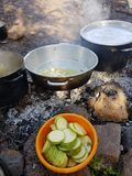 A big pan with Fried onion and zucchini in an orange plastic. Camp cooking in the field on open fire - a big pan with Fried onion and zucchini in an orange Royalty Free Stock Images