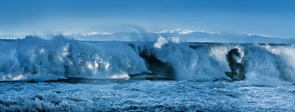 Big panorama with high stormy waves and snow-capped mountains Royalty Free Stock Photos