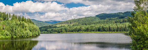 Big panorama of mountain lake between forests Stock Images