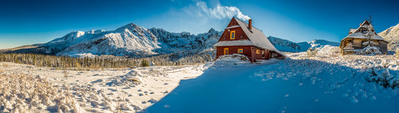 Big panorama of mountain small cottage in a winter dawn Royalty Free Stock Images