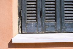 Big part window with a shutters on house facade Stock Images