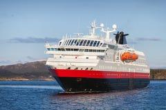 Big passenger cruise ship sails in fjord. Big Norwegian passenger cruise ship sails in fjord royalty free stock photo