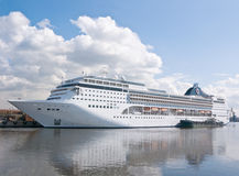 The big passenger ship in the trade port. The big wkite passenger ship in the trade port and clouds Royalty Free Stock Photos