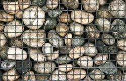 Big pebble stones in iron mesh background texture. Pebble stones in iron mesh background texture Royalty Free Stock Photos
