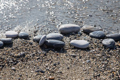 Big pebble on a wet sand seacoast. Focuse on central stone Royalty Free Stock Photo