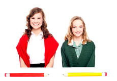 Big pencils lying in front of two school girls Stock Photos
