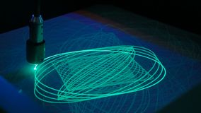 Big pendulum draws ellipses with light on phosphorus surface. Science, physics and experiment concept stock photography