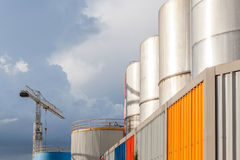 The big petrol oil tanks and hoisting crane againt blue sky in r Royalty Free Stock Photos