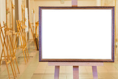Big picture frame on easel in gallery hall Royalty Free Stock Image