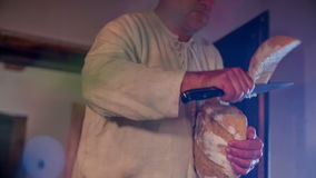 Big piece of bread for a man. Close up slow motion RAW footage of a waiter cutting the piece of bread and giving it to a man seating at the table stock video