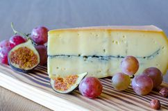A big piece of cheese, grapes, nuts, sliced figs on wooden tabl stock photo