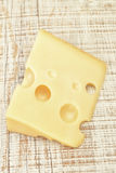 Big piece of cheese on a textured board. Royalty Free Stock Images
