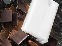 Big piece of coconut fat coming together with chocolate. Big piece of coconut fat coming together with light and dark chocolate in a glass bowl stock photo