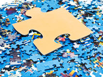 Big piece on pile of disassembled puzzles Stock Image