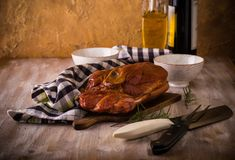 Big piece of smoked pork meat on vintage chopping board. Horizontal photo with big piece of smoked pork meat with bone placed on cutting board. Blue towel Stock Images