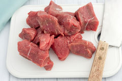 Big pieces of  of raw beef on white choping board Stock Image