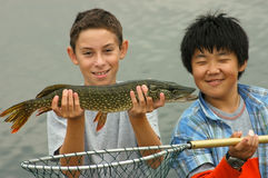 Big Pike. Two young teenage male friends showing off their captured pike. Asian and caucasian models; pictures are model released Stock Photography