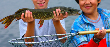 Big Pike. Two smiling teenage friends, Asian and Caucasian, show off their fishing catch Royalty Free Stock Photos