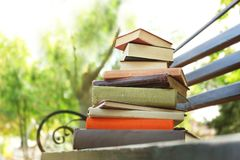 Pile of books on bench in a park. Big pile of books on bench in a park royalty free stock photography
