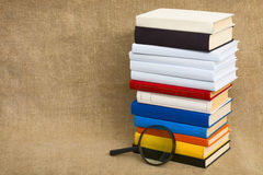 Big pile of books and magnifier glass Royalty Free Stock Image