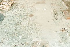 Big pile of broken and shattered window glass on the floor of the house demolished after earthquake or hurricane natural disaster. In the city royalty free stock photos