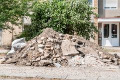 Big pile of cement concrete and dirt on the street in front of the residential building left as remains of the apartment renovatio royalty free stock image
