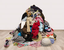 Big pile of clothes and accessories thrown on the ground. Untidy cluttered wardrobe with colorful clothes and accessories Royalty Free Stock Photos