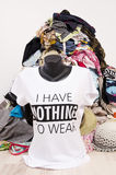 Big pile of clothes thrown on the ground with a t-shirt saying nothing to wear. Stock Image