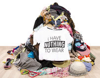 Big pile of clothes thrown on the ground with a t-shirt saying nothing to wear. Royalty Free Stock Photo
