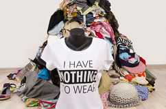 Big pile of clothes thrown on the ground with a t-shirt saying nothing to wear. Stock Images