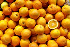 Oranges pile. Big pile of fresh oranges with one on the top cut in half stock photo