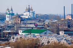 Big pile of logs and two churches. Tyumen. Russia Stock Image