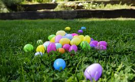 Big Pile of Plastic Eggs. Brightly colored plastic eggs scattered on a green grass on a sunny afternoon. Close up Royalty Free Stock Photography