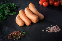 Big pile of raw short sausages with rucola and tomatoes. Big pile of raw short thick sausages with pink salt, spices, green rucola and tomatoes cherry on black stock photos