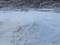 A big pile of snow near the road. Its white and cold, and tire marks are visible on the road Stock Photography