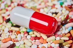 Big pill and many colorful medicines royalty free stock photography