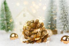 Big pine cone with golden garland lights in winter scene in forest with fir trees falling snow. Christmas New Years holiday magic. Atmosphere. Greeting card stock images