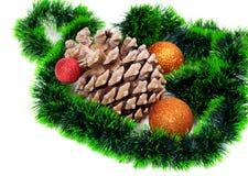 Big pine cone, green Christmas tinsel and Christmas-tree balls Stock Photography