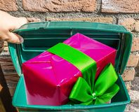 Big pink Christmas present with ribbon in a classic green mailbox. A Big pink Christmas present with ribbon in a classic green mailbox royalty free stock photo
