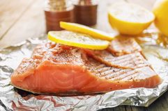 Big pink piece of salmon with herbs and lemon rests on a shiny piece of foil. Stock Photos
