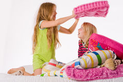 The big pink pillow. Two young children enjoying their colorful bed stock photo