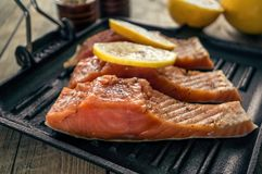 Big pink slice of salmon with herbs and lemon rests on a black grill pan. Stock Photography