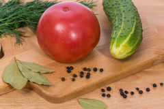 The big pink tomato cucumber dill and black pepper. Close-up. The big pink tomato cucumber dill and black pepper. They lie on a cutting board Royalty Free Stock Photo