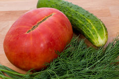 The big pink tomato cucumber and dill. Close-up. The big pink tomato cucumber and dill, lie on a cutting board Stock Photos